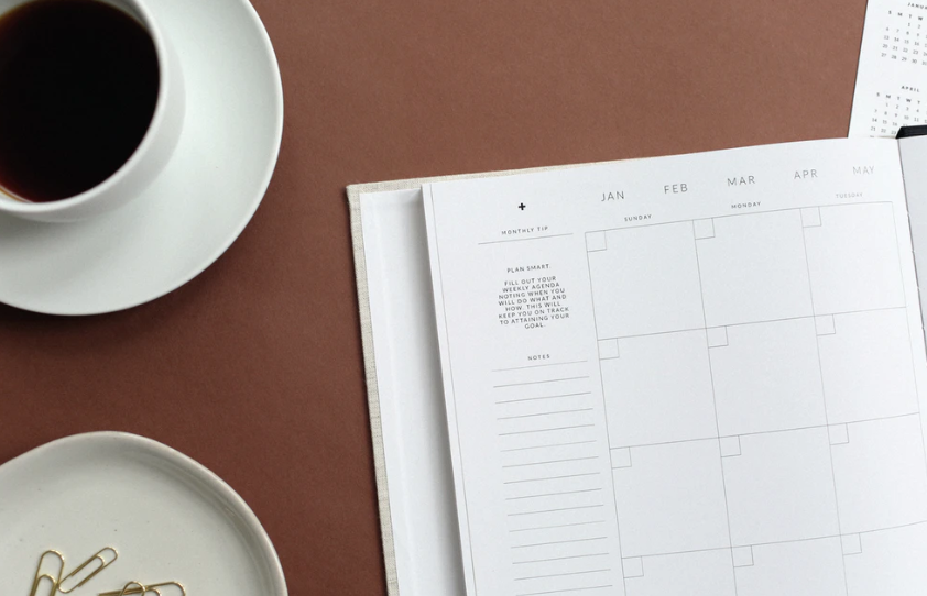 calendar planner and cup of coffee on table.